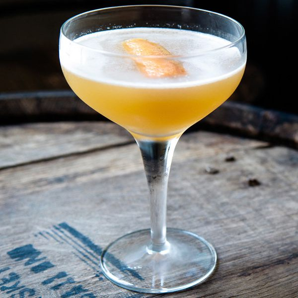 brown derby cocktail in a coupe, served on a wooden barrel