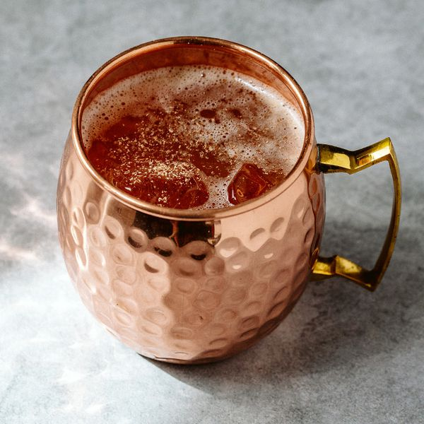 A hammered copper mug rests on a marble counter. Ice and a drink fill the cup, and it's garnished with a dusting of nutmeg.
