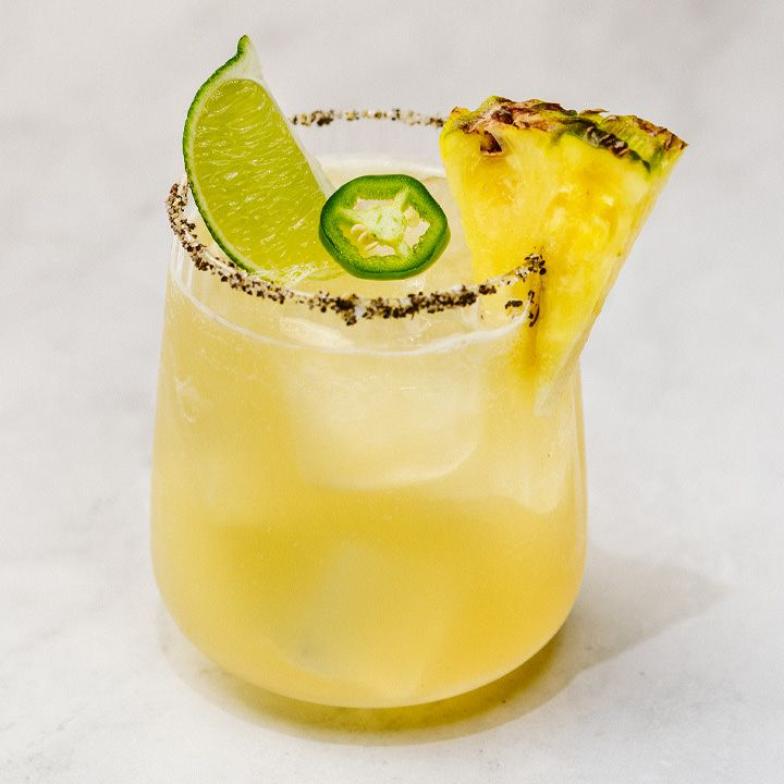 yellow-hued Pineapple Jalapeno Margarita in a sugar-and-black-pepper-rimmed rocks glass, garnished with pineapple, lime wedge and jalapeño slice