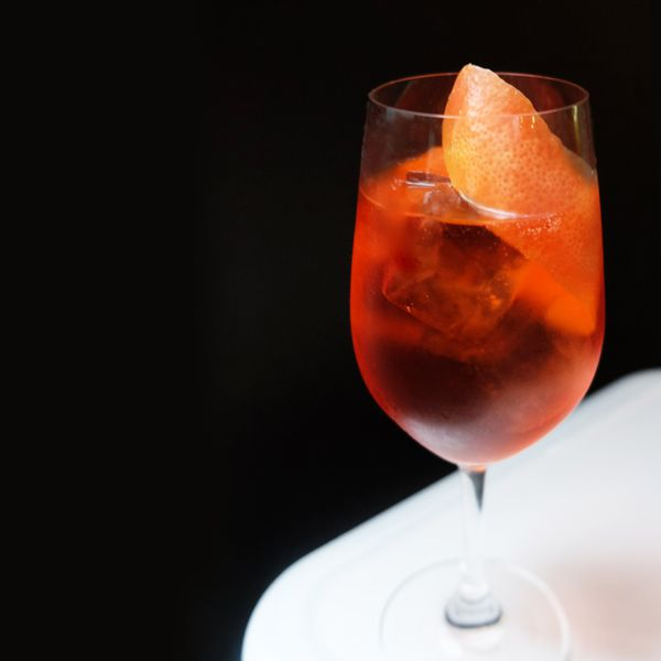 On a white table with a solid black backdrop sits a loan, high walled wine glass. It's filled with a red-orange liquor and a few ice cubes, with a long grapefruit peel garnishing it.