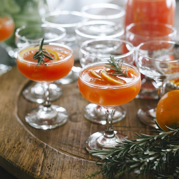 orange cocktails in coupe glasses with rosemary