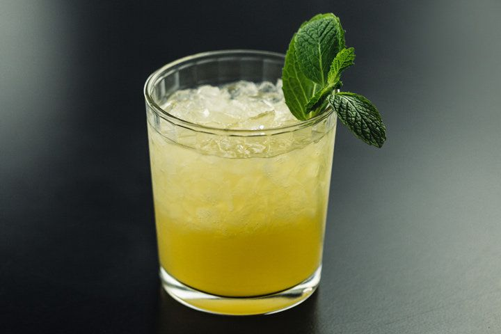 A golden-yellow Mai Tai on crushed ice in a beveled clear rocks glass and garnished with a fresh mint sprig