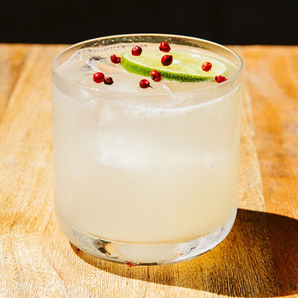 Pink Peppercorn Botanical Gimlet garnished with lime wheel and peppercorns