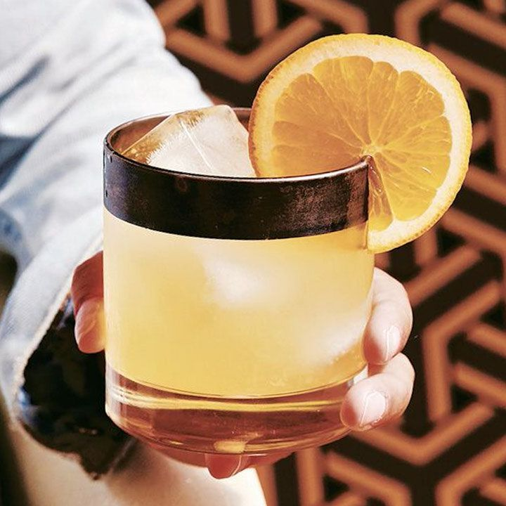 A person's hand holds a rocks glass with a thick copper rim. The glass holds three large ice cubes and an orange drink and is garnished with an orange wheel.