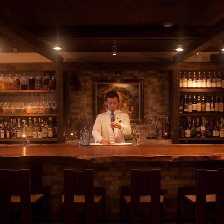 Bar Benfiddich in Tokyo. A lone bartender stands in the center of the frame, behind a abr. he is in a white blazer and is stirring a cocktail.