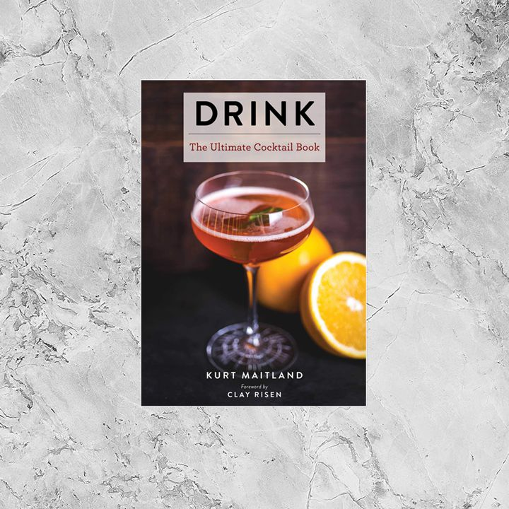 Drink: The Ultimate Cocktail Book cover, dark brown background with a red cocktail in a coupette sitting on a black surface next to a halved orange. Cover is framed by a gray and white ice-textured composite background