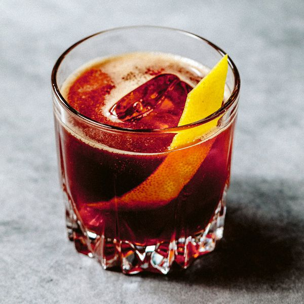 A rocks glass rests on a gray marble surface. The glass is filled with a dark red opaque drink over a large ice cube, and is garnished with a thin slice of lemon peel.