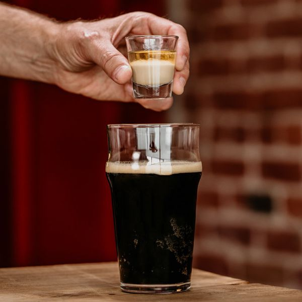 hand holding a shot glass over a pint of Guinness to make an Irish Shot