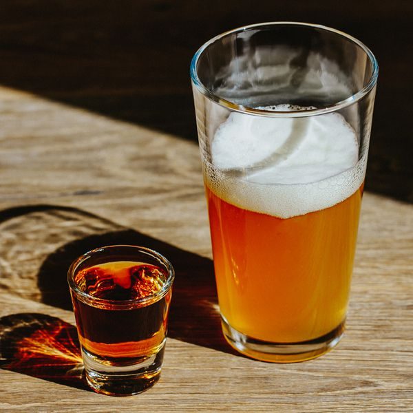 Boilermaker cocktail with half-full beer next to a whiskey shot