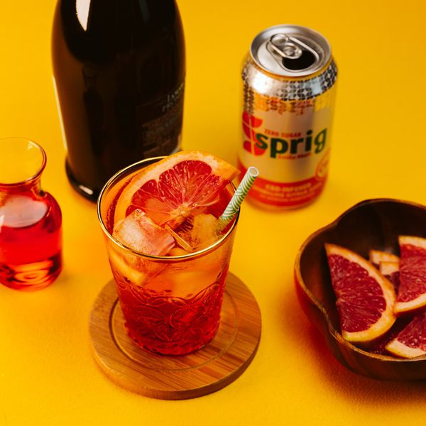 CBD Spritz cocktail on a wooden coaster, garnished with a grapefruit slice and straw, served next to a Sprig CBD can