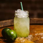 A Mason jar with a light green cocktail, crushed ice and a paper straw with limes and more crushed ice placed beside it