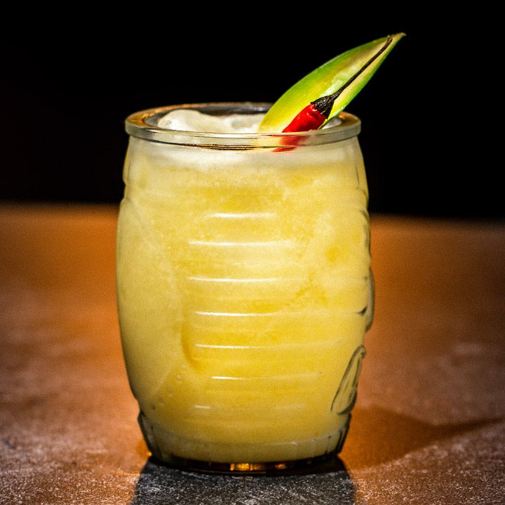 Against a black background, a curved cocktail jar rests on a dark surface. It's filled with an orange colored hazy drink and ice cubes and garnished with a Thai chili pepper and a pineapple frond.