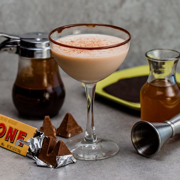toblerone cocktail beside toblerone chocolate bar and honey syrup