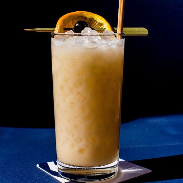creamy, orange-hued cabana boy cocktail, served in a highball glass over pebble ice and garnished with a skewered cherry and orange wheel