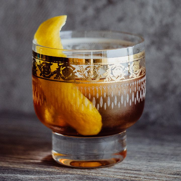 vieux carre cocktail in gold-laced glass with lemon peel garnish