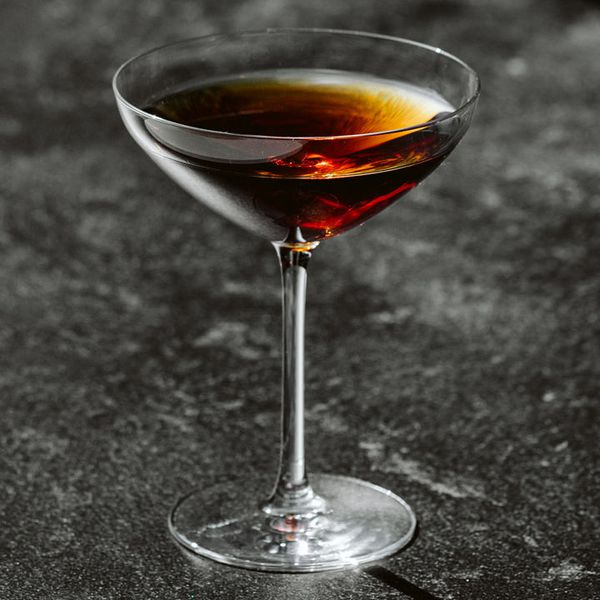 McKInley's Delight cocktail in a stemmed cocktail glass on a dark gray granite surface