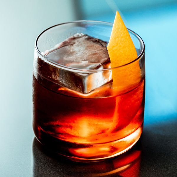 boulevardier cocktail over one large ice cube and with an orange peel garnish