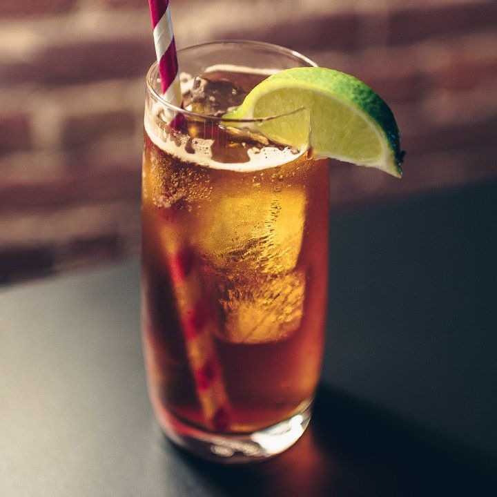 chinese 5 spiced dark 'n stormy cocktail in a collins glass, garnished with a lime wedge and served with a red-and-white straw