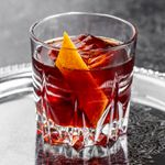 A crimson-hued Negroni on a large ice cube in a chunky rocks glass rests on a silver platter.