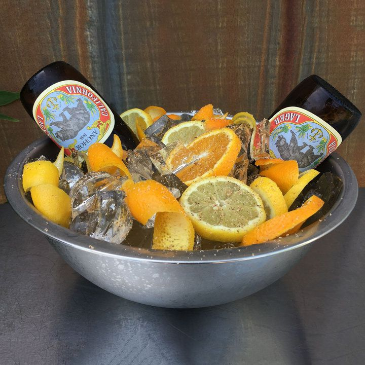 A metal bowl is filled with ice, citrus slices, orange peels and two upended bottles of lager. The bowl is in front of a wooden fence.