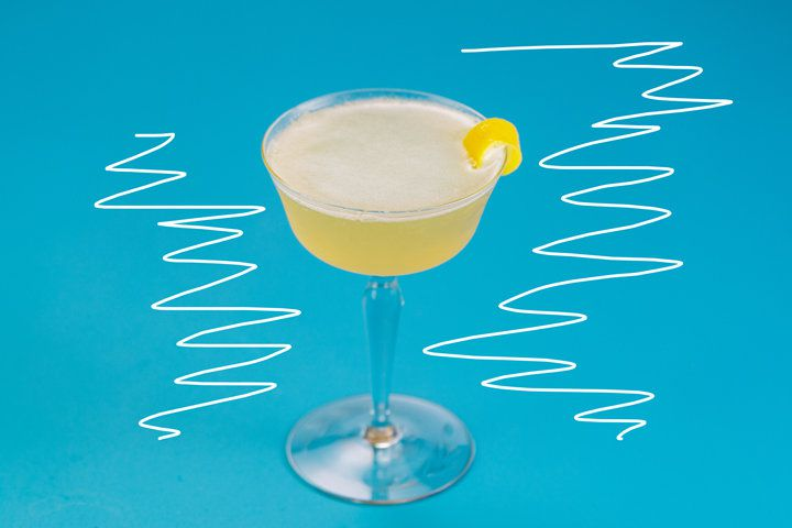 A shaken yellow cocktail served up in a wide coupe and garnished with lemon zest