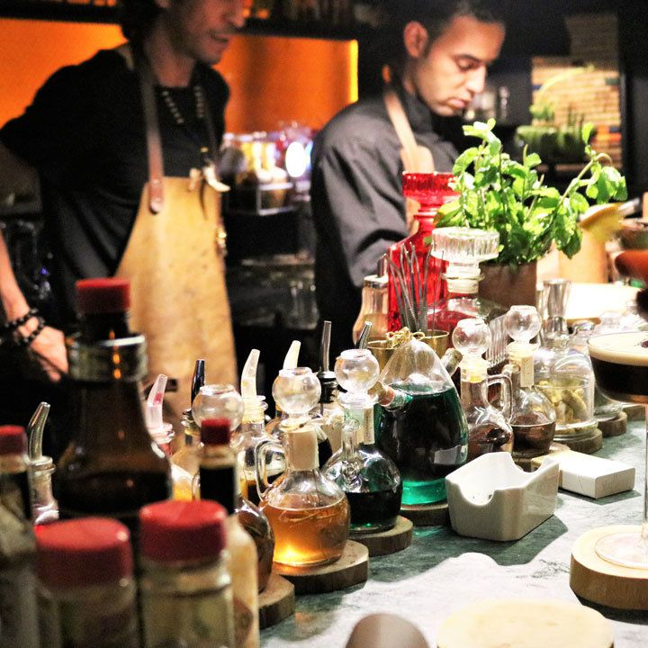 Baromètre Cocktail Lounge. Two bartenders, each in leather aprons, are preparing drinks behind a collection of tinctures and herbs