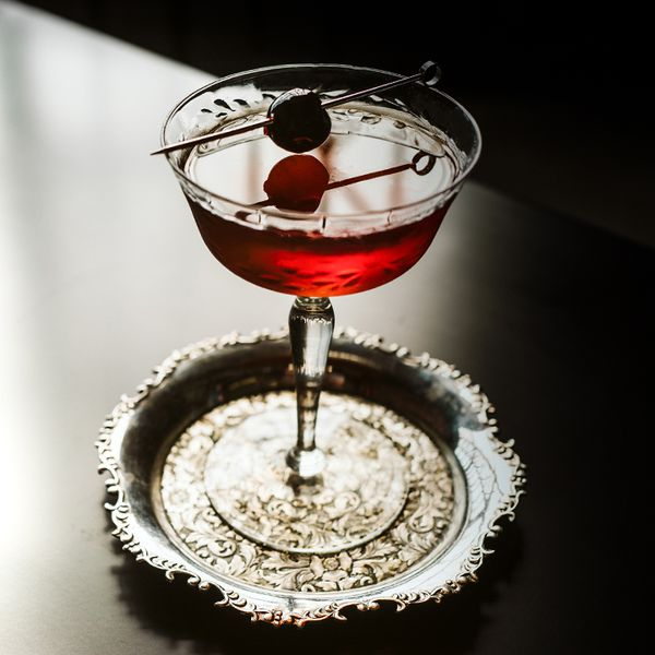 a la louisiane cocktail with cherry garnish served in a coupe glass on an ornate round metal coaster