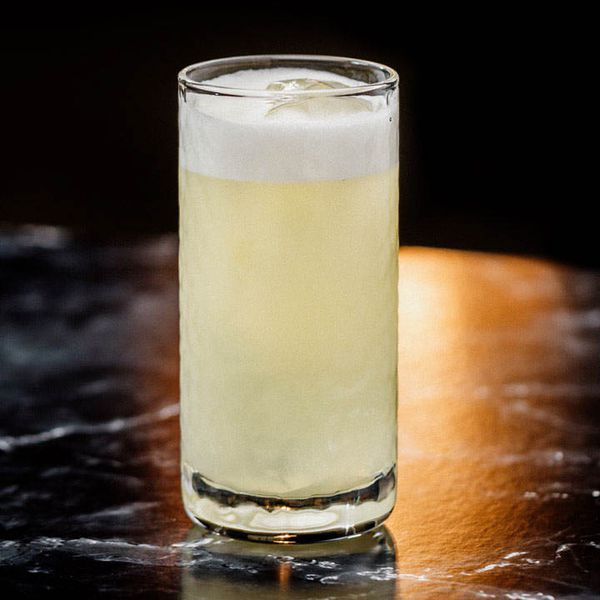 A highball glass is filled with a light gold cocktail topped with foam. The drink rests on black marble, and the background is solid black.