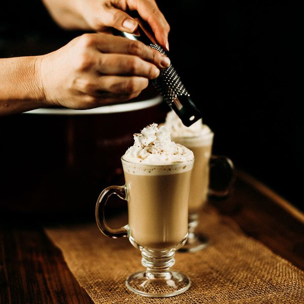 hands grating nutmeg over two pumpkin spiced latte cocktails