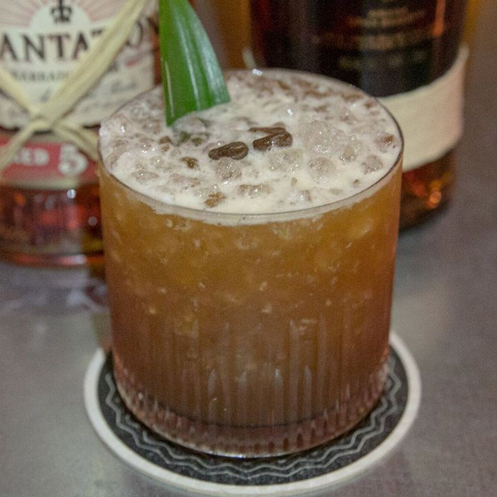 A short glass is filled with crushed ice and a brown rum drink. A single pineapple leaf garnishes the drink, and in the background there are bottles of Plantation and Ron Zacapa rums.