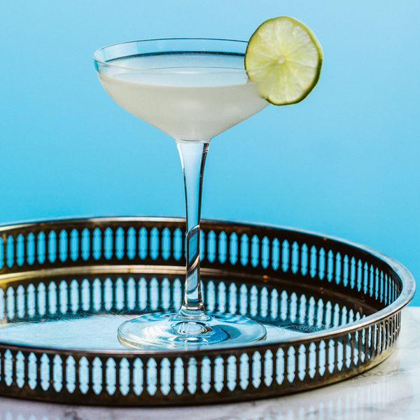 Gimlet cocktail on a circular tray and garnished with a lime wheel