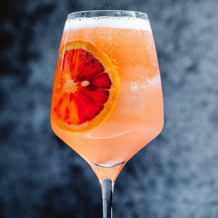 A pale orange spritz is held in a stylish wine glass, with a large, flat wheel of blood orange pressed up against the wall of the glass. The background is dark and out of focus, amplifying the drink.