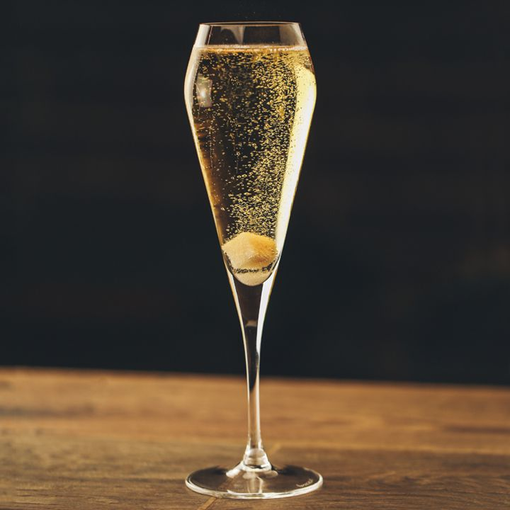 My Golden Dram cocktail in a Champagne flute with a sugar cube at bottom and tiny bubbles floating upward, served on wooden surface