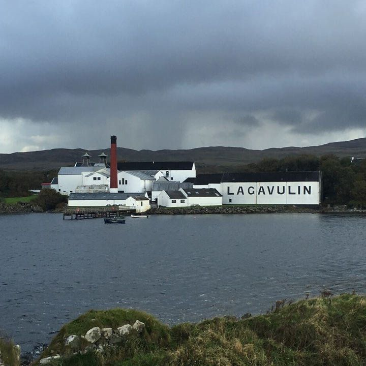 Lagavulin Distillery, seen from far away with the full whitewashed distillery in the background voer open water