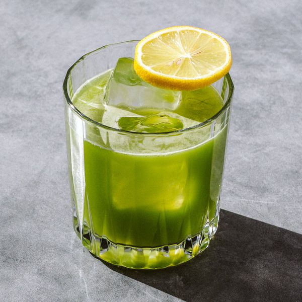 green-colored Green Tox cocktail in a rocks glass with ice cubes and a lemon wheel balanced on the rim, served on a sunny gray surface