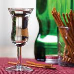 A stemmed tasting glass filled with genever in front of a cup of pretzel sticks