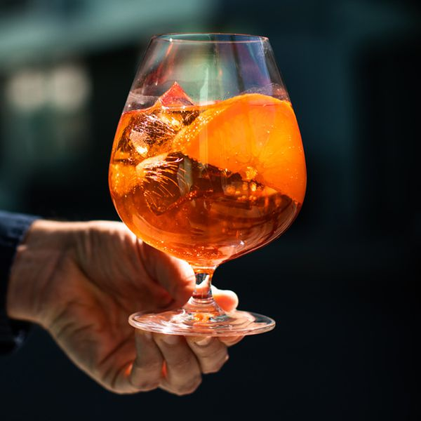 A man's hand holds a goblet filled with ice and the amber glow of an Aperol spritz. A large slice of orange rests atop the ice
