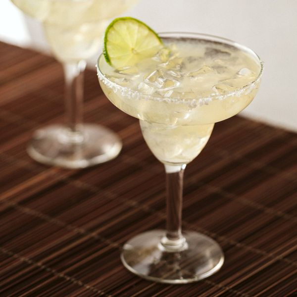 Margaritas by the Pitcher served in Margarita glasses on a brown bamboo mat