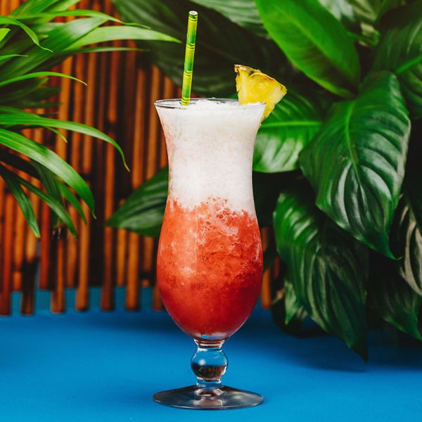 miami vice cocktail on blue surface with green plants