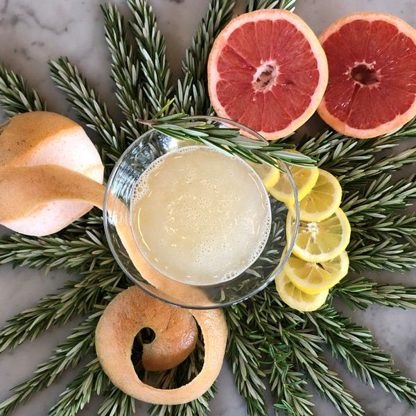 A pale cocktail in a Martini glass is centered in a top-down photo. Surrounding it is a wreath of rosemary, as well as a partially peeled grapefruit, a lemon sliced into rings, and a halved grapefruit. The background is marble.