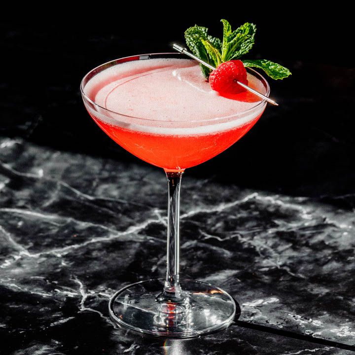 A wide, shallow and slightly curved Martini glass holds a vividly red cocktail. The drink is garnished with a sprig of mint and a raspberry on a silver pick. The surface below is black marble, the background solid black.