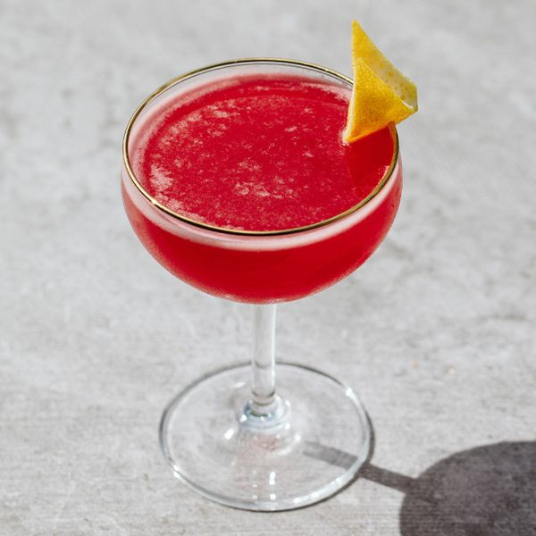 deep-red bebbo cocktail in a coupe, garnished with a lemon twist and served on a gray surface