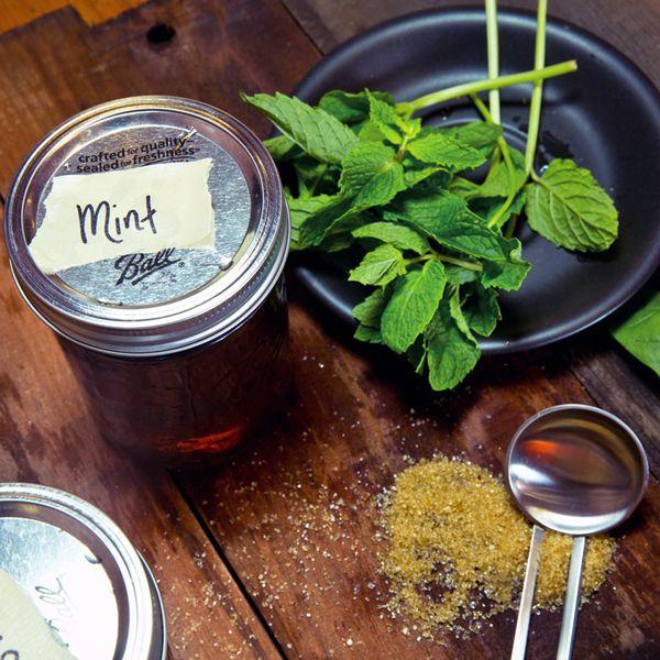Mint simple syrup in Mason jar beside mint leaves and turbinado sugar