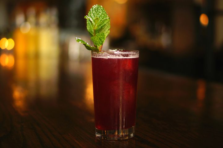 A deep, dark red cocktail in a collins glass is garnished with a sprig of mint. The cocktail sits on a dark, hardwood bar.