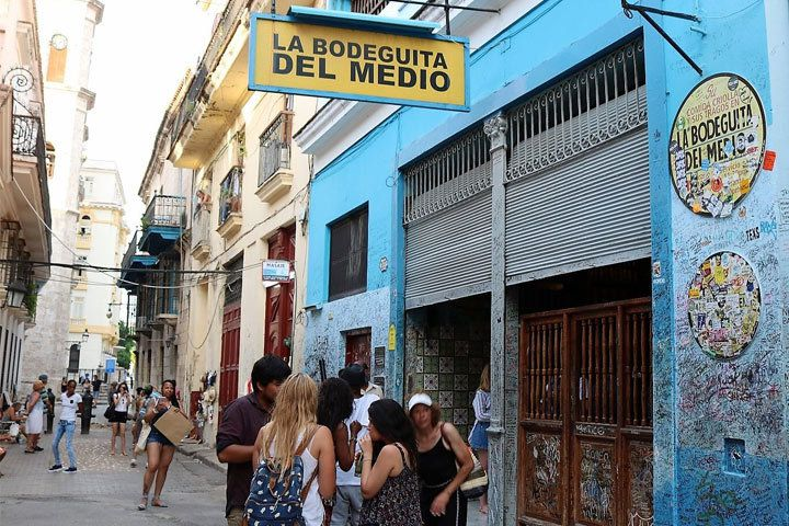 A small crowd gathers in the day time outside of La Bodeguita Del Medio, a bar in Cuba. Its walls are pale blue and covered in markings.