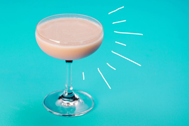 A curved coupe glass holds a white, creamy cocktail. The glass rests on a pale blue background, with a few dramatic white lines emanating from it.
