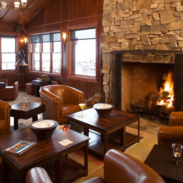 The Resort at Paws Up lobby lounge with a roaring fire in the fireplace and a cabin/lodge look