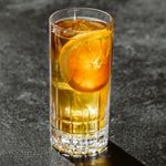 Sherry Cobbler over ice in a textured highball glass, with an orange wheel pressed against the inside of the glass