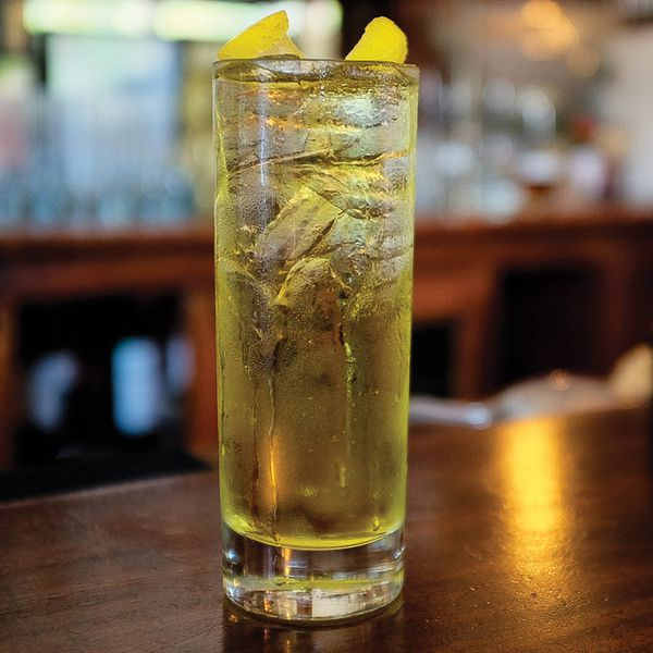 A light yellow cocktail on ice in a highball glass garnished with grapefruit zest