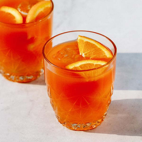 Two etched glasses hold a bright orange punch and two slices of orange. The glasses cast long shadows on a pale marble countertop.